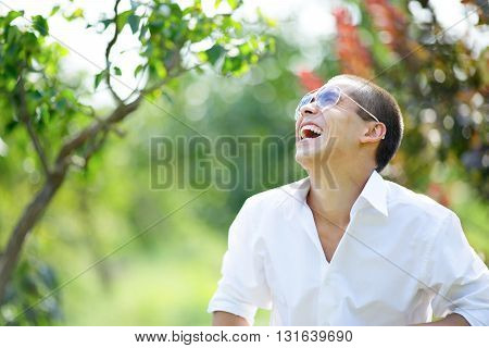 Laughing young man in sunglasses. The outdoor