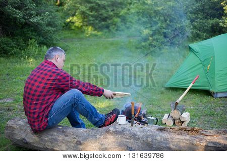 Man drinking coffee by the fire at a campsite on the river bank