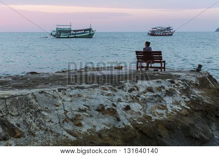 Lonely woman sitting on the rocky shore and watching the twilight sea.