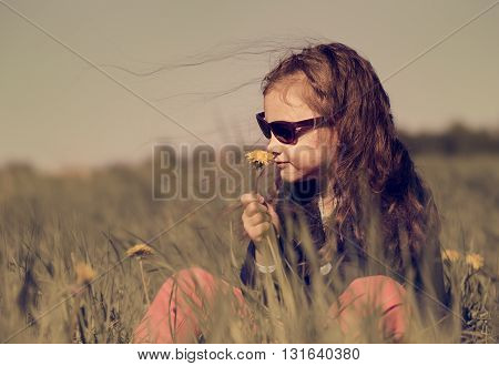 Fashion kid girl sitting on the grass in sunglasses on summer background