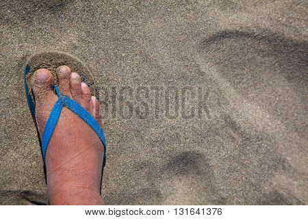 Feet of a man in thong sandals in beach sand