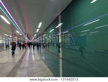 Vienna, Austria. January 2015. People walking through subway tunnel with ceiling light lines and reflections.