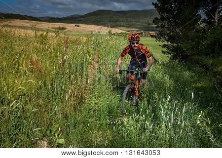Bibbona Tuscany Italy - May 24 2016: lifestyle using the mountain bike to ride in the paths of Tuscany and of the protected natural area of the Macchia Magona