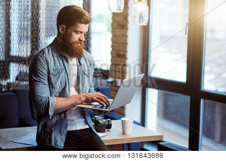 Contemporary vision. Pleasant delighted handsome smiling bearded man  leaning on the table and using laptop while being involved in work