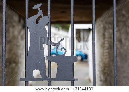 Photo of symbolic blacksmith on iron fence