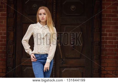beautiful young blonde girl in jeans standing near ancient door