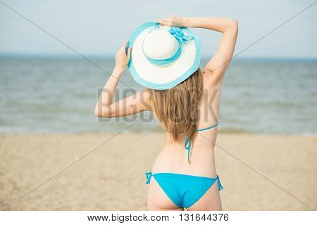 Young lady sunbathing on a beach. Beautiful woman posing at the summer sand beach. Outdoor summer portrait of pretty sport style woman in blue bikini. Ocean sea coast. Beautiful fit tan girl. Sexy slim model caucasian ethnicity outdoors.