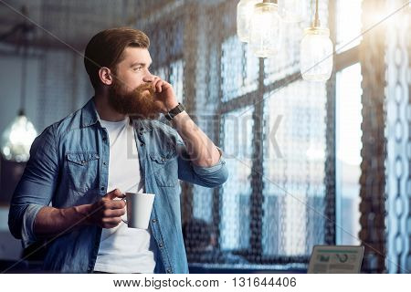 Nice to hear you. Cheerful delighted handsome bearded man talking on cell phone and drinking coffee while resting in the office