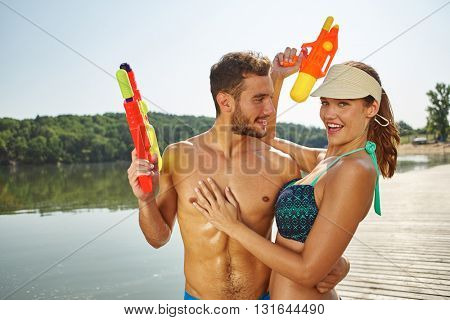 Couple at a lake having fun with squirt guns in summer