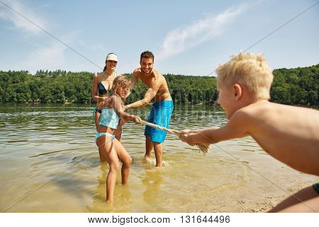 Happy family pulling the rope at the lake in summer