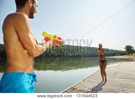 Happy couple at a lake spraying each other with a water gun in summer