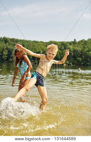 Two happy kids splashing and playing with the water in summer