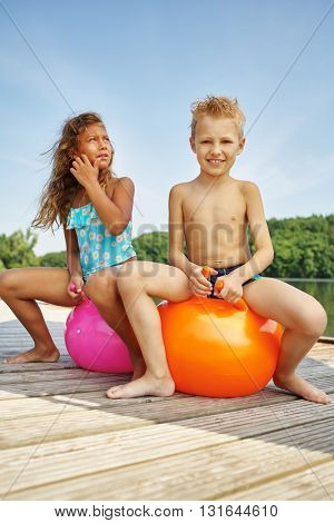 Two happy kids sitting on spacehoopers at a lake on their holidays