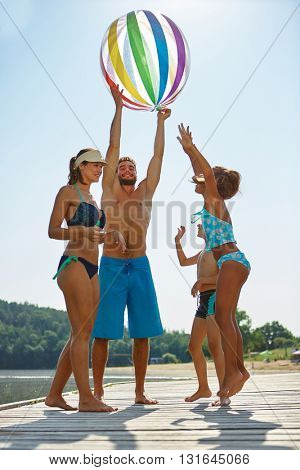 Happy family having fun with a beach ball at a lake in summer