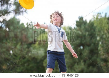 Boy throws flying disc in summer in the nature
