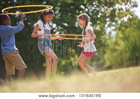 Group of happy kids plays with hoops
