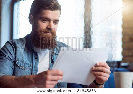 My everyday work. Pleasant glad handsome delighted bearded man sitting at the table and holding papers while  being involved in work