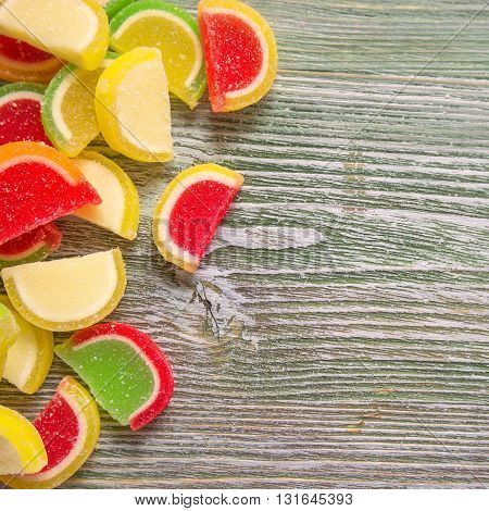 Sweet tasty vibrant candies, top view. Wooden background with copyspace