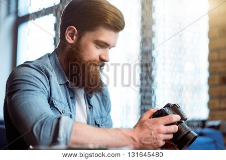 Nice pics. Pleasant cheerful smiling bearded man sitting at the table and holding photo camera while expressing gladness