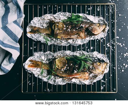 Grilled fish with spices on fire. Cooking background