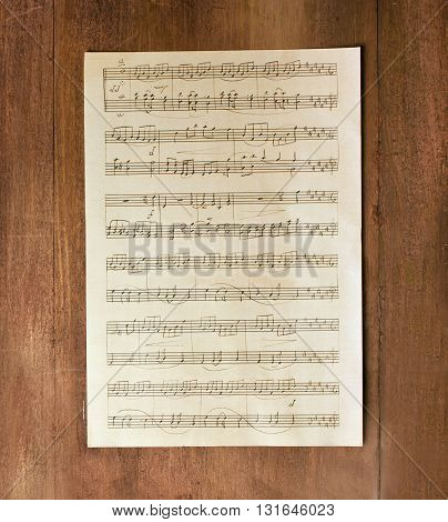 A piece of aged sheet music shot from above on a dark brown wooden texture; a background for a design
