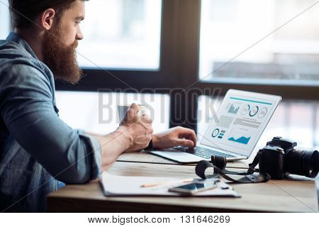 Work with inspiration. Pleasant cheerful bearded glad man sitting at the table and working on the laptop while drinking coffee