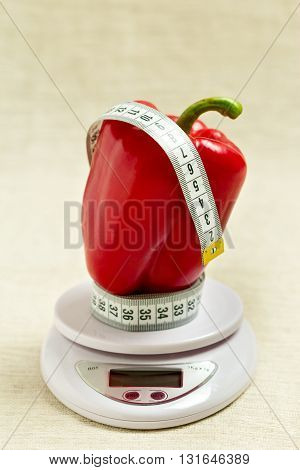 Concept of diet health. Red sweet bell pepper with a meter on the white balance. Selective focus.