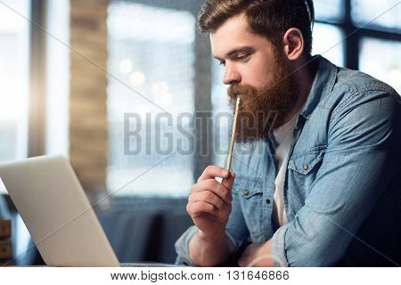 Let me think.  Serious concentrated man  sitting at the table and working on the laptop while thinking