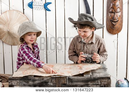 two little children in hats watching map on big old chest