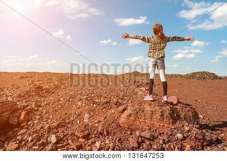 girl standing on large stone in iron mineral ground area from back with hands wide open