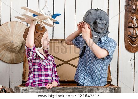 smiling little girl with wooden plane in hand and boy in pilot hat sitting in big chest