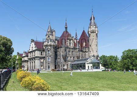 MOSZNA - MAY 22: View of the Thiele-Winckler Palace on 22 May 2016 in the district Moszna, Poland. Tourists enjoying the beautiful weather visit the palace in Moszna.