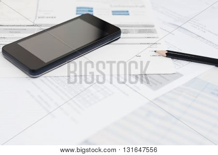 Bill and smart phone with pencil, Bill for income and expenditure with tax bill, Selective focus
