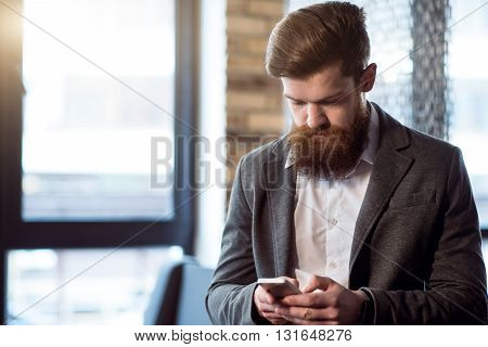 Seriousness in mind . Pleasant brutal handsome bearded man  holding cell phone while typing message