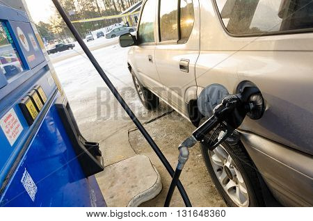 Charlotte, NC, United States - 01-25-2016: Fuel nozzle in the tank at the gas station. Car refueling concept.