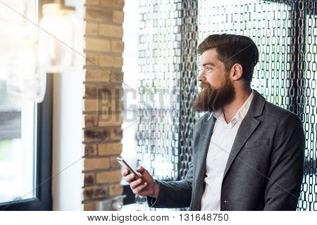 Have a look. Pleasant delighted positive man holding cell phone and looking in the window while standing in the office