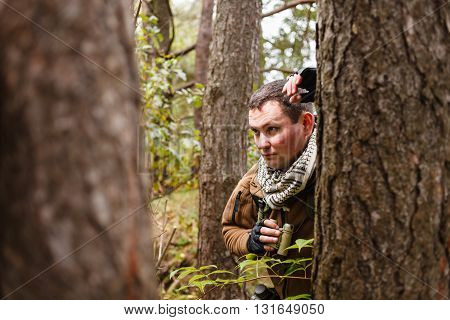 Caucasian man with binoculars at a forest.