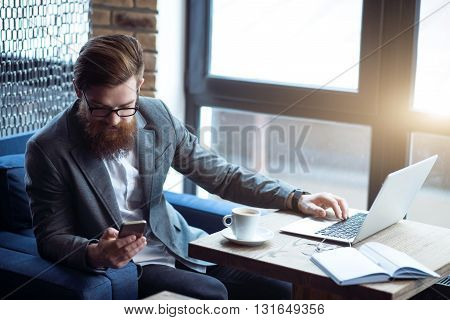 Modern user. Pleasant bearded handsome man sitting at the table and holding cell phone while using laptop