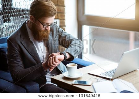 In a good mood. Pleasant delighted handsome bearded man sitting at the table and feeling glad while using his smart watch
