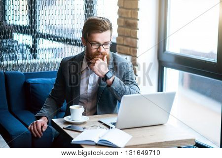 Involved in thoughts. Pleasant concentrated bearded man sitting at the table and looking at the laptop while thinking