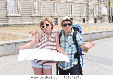 young tourist couple visiting Madrid in Spain lost and confused loosing orientation with boyfriend carrying travel backpack and girl holding city map in holiday trip and vacation concept