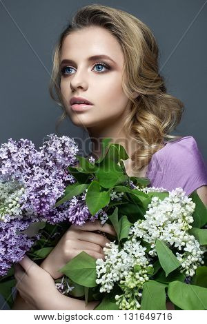 Beautiful girl in a purple dress and a bouquet of lilacs. The model in image spring. The photo was taken in a studio.