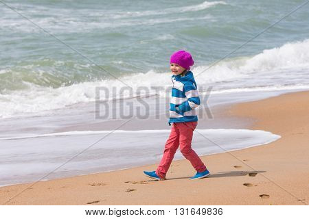 Happy Girl Walking Along Coastal Sea Beach On A Warm Spring Day