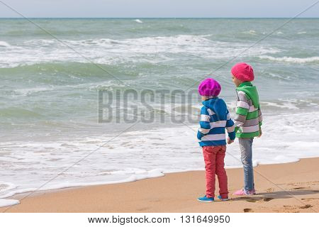 Two Girls Holding Hands Standing On The Beach And Looking Into The Distance