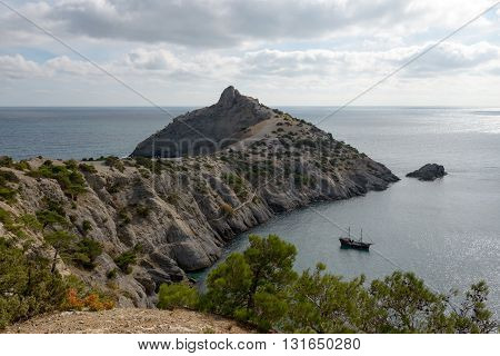 High angle scenic view towards Kapchik Cape is from cliff above Light Blue or King Bay or Delimanskaya Cave on northern side of headland near New World (Novyi Svet) town Crimea Russia.