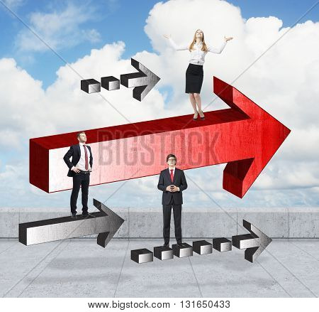 Success concept with young businesspeople on arrows on concrete ground and sky background
