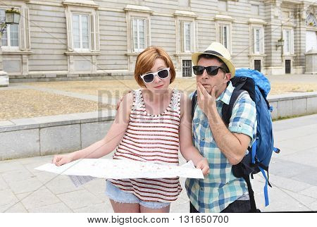 young tourist couple reading city map looking lost and confused loosing orientation with girl carrying travel backpack and man in frustrated face expression while visiting Madrid in Spain