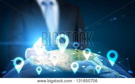 Traveling concept with businessman pointing at globe with location pin network on dark background.