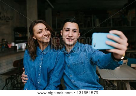 handsome guy and beautiful girl making selfie indoors