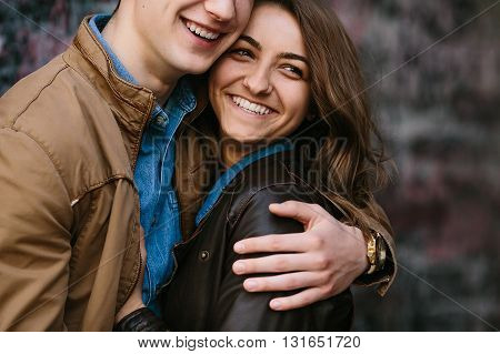 handsome guy and beautiful girl posing against the backdrop of the board with the words